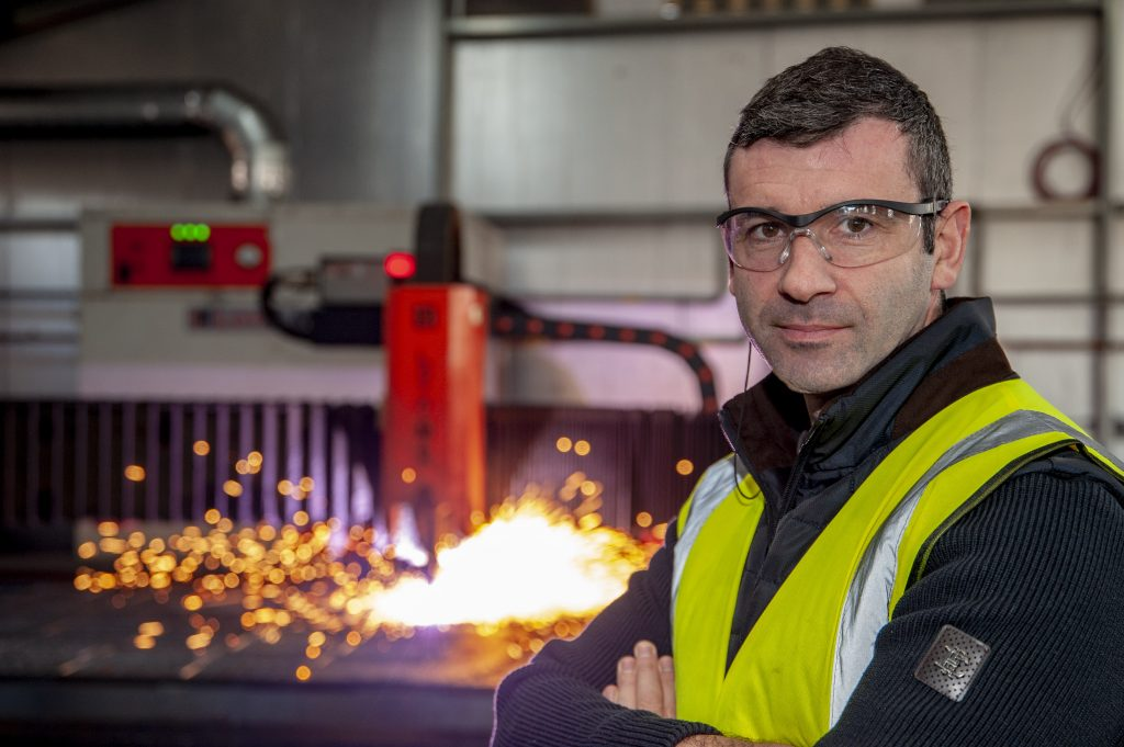 Sparks fly from a laser cutting steel behind Liam O'Sullivan, owner of Irish Rollforming, a Cork based universal cladding solutions company.
